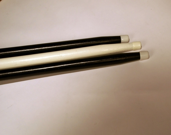 Two black wooden canes and one white painted wood
